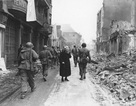 Standing between advancing U.S. Seventh Army troops, an old German Woman in despair surveys the hopeless wreckage of her home. XV Corps 3/27/1945.